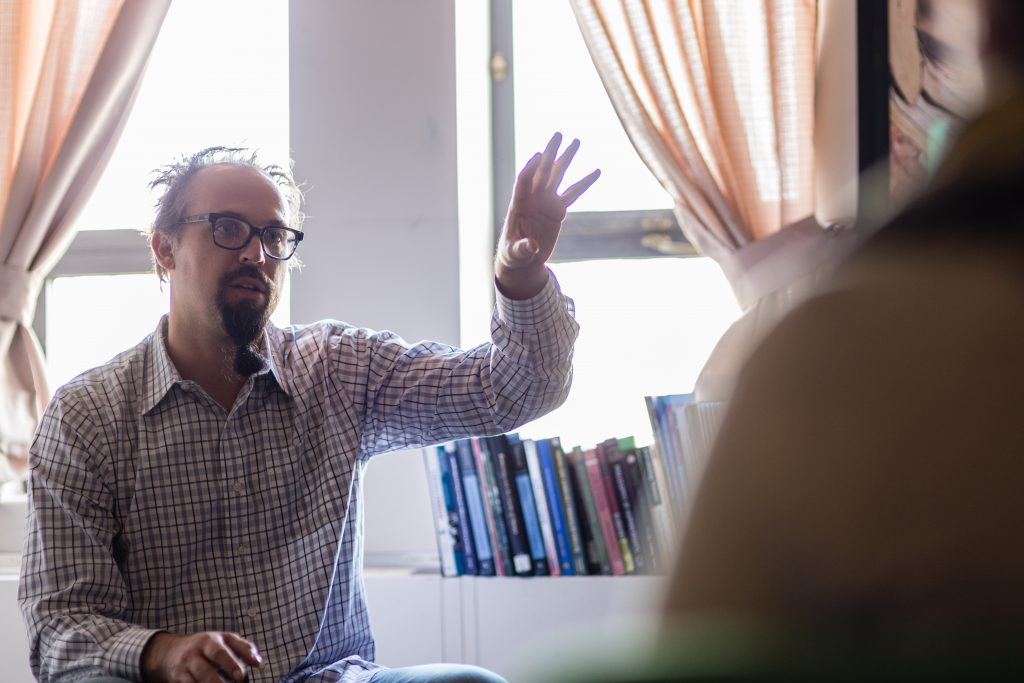 Man wearing a checkered dress shirt and black rimmed glasses. His left arm is raised in the air and he is talking to someone