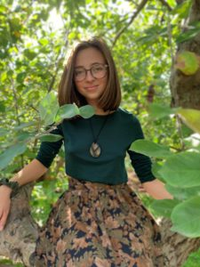 woman wearing glasses and a green shirt and floral skirt standing in trees